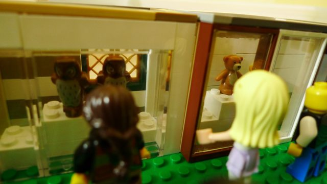 minifigures looking at owls and bear on exhibit